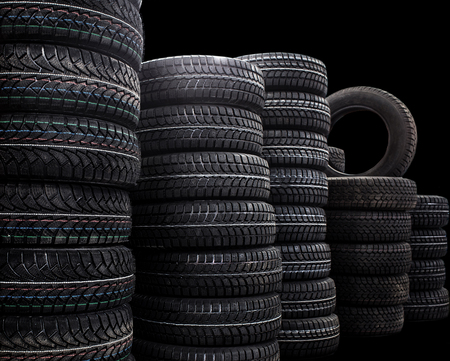Warehouse of new tires. Isolated dark background. Black and white