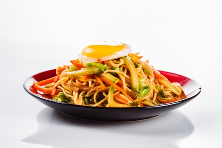 noodles with bacon, fried egg and pepper on a red plate on a white background. Traditional Italian pasta. Close Reklamní fotografie