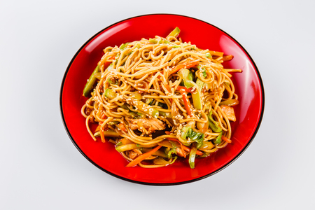 Noodles with pork, pepper and sesame seeds on a red plate on a white background. Traditional Italian pasta. Close