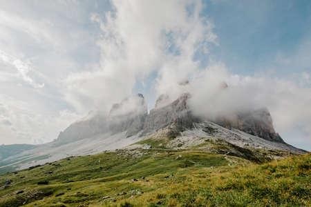 Italian Dolomites, Tre Cime - Rifugio Lavaredo - stony road around Tre Cime .Peak in the clouds. Aerial shot. Beautiful sky and clouds behinds the moutains and valley. Banco de Imagens