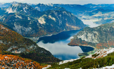 View from above to Hallstatter lake and Hallstatt village among Alps mountains in Austria. Beautiful nature landscape. Autumn season and trees with orange colour. Wonderful valley of rocks and ridges.