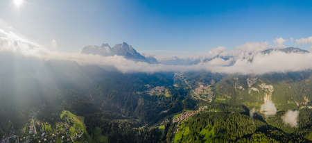 Italian Dolomites mountain valley with town in the country. Aerial beautiful shot above the clouds. Green hills with buildings. Tiled roofs on the houses. Fields with forests.