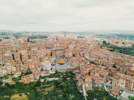 Panoramic aerial shot of Siena, cityscape, a beautiful medieval town in Tuscany, with view of the Dome Bell Tower of Siena Cathedral, landmark Mangia Tower and Basilica of San Domenico, Italy