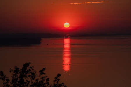 Beautiful low key sunrise with early sun and structure reflections. Sunset above the horizon. Nature landscape at the morning. Meditation and relaxation.