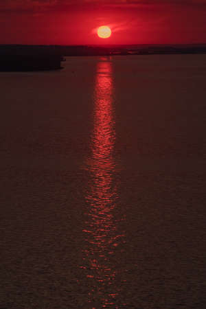 Beautiful low key sunrise with early sun and structure reflections. Sunset above the horizon. Nature landscape at the morning. Meditation and relaxation. Vertical shot.