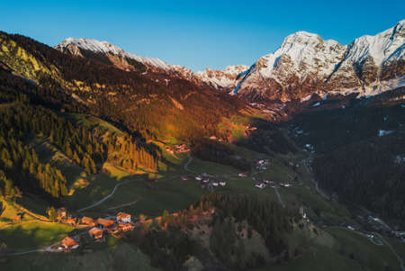 Beautiful nature lanscape in Italian Alps, Dolomiti.Italy. Mountain range with snowy peaks on the sunset light. Big shadow on the valley. Structure rocks. Aerial panoramic shot. Postcard concept.