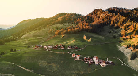 Beautiful nature lanscape in Italian Alps, Dolomiti, Italy. Houses at the sunset light. Big shadow on the valley. Structure forest. Aerial panoramic shot. Postcard concept. Stok Fotoğraf