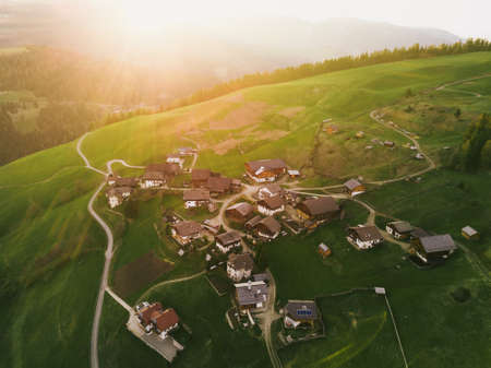 Beautiful nature lanscape with sunlight in Italian Alps, Dolomiti, Italy. Houses at the sunset light. Big light on the valley. Aerial panoramic shot. Postcard concept.