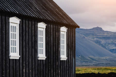 Black churc in Iceland. Close up of black walls and white window platbands. Icelandic scenic travel destination of religion. Christianity and religious concept. Postcard theme.Mountains on background. Stok Fotoğraf