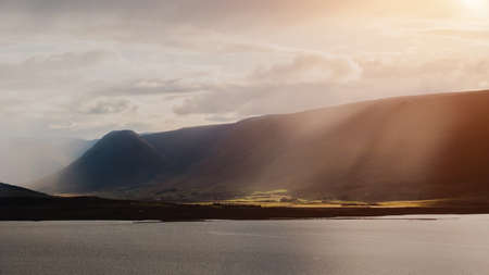 Beautiful panoramic sunset view to the mountains with sun light from the clouds. Epic and amazing dramatic landscape picture.Postcard theme of Iceland. Nature and ecology concept background.