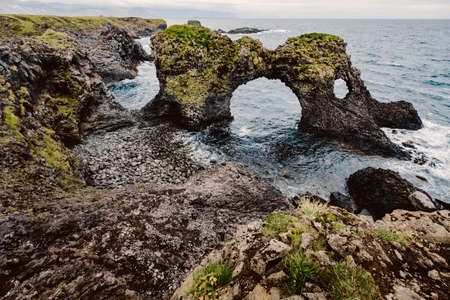 Amazing seascape, Gatklettur basalt rock arch at the volcanic cliff, Atlantic coast of Arnarstapi in the west of Iceland, natural background. Postcard concept. Rocks and stones with abstract forms.