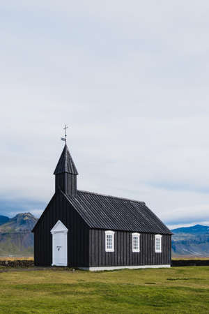 Black church in the meadow and field in Iceland. Icelandic scenic travel destination of religion. Christianity and religious concept. Postcard theme. Praying in chapel.Mountains on background.