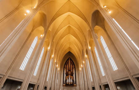 Hallgrimskirkja church indoor interior. Beautiful big arch view. Organ musician instrument. Symmetry modern high hall. Place for the praying.