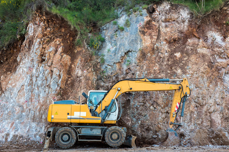 Yellow digger standing at the wall mountains Stock Photo