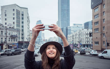 Girl is photographing city streets., day, close up . Brown-haired girl in a gray coat and hat, enjoying a walk, on a cloudy day, in the city center. Slightly girl holding the phone with both hands