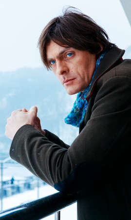 greenish blue: Middle-aged man in a blue scarf and a greenish coat. Man with beautiful big blue eyes Stock Photo