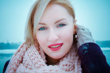 Young woman blonde who wears a big  pink bouffant scarf, day, outdoor . violet coat
