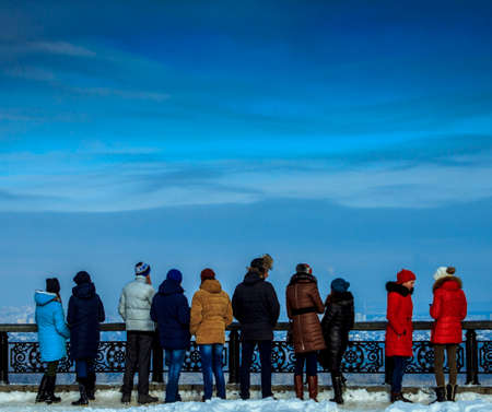 People in colorful winter clothing, enjoy views of the city, against the backdrop of beautiful clouds