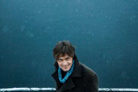 Brunette man in winter overcoat  looking into camera, top view.