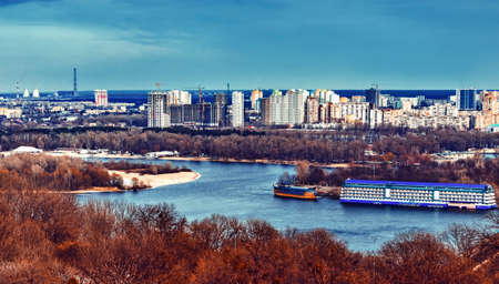Ukrainian Dniper river on the background of Kiev cityscape, buildings, poisoned emissions. Trees in foreground