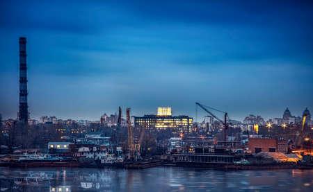 Mine smoke waste, and cranes in the port city. Night Cargo Port Work in Kiev Stock Photo