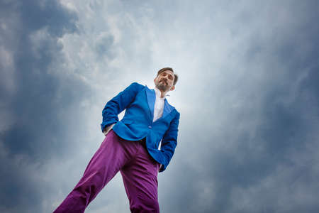 Man in a blue jacket and purple trousers. Middle-aged man standing with a form of superiority. Super low camera angle. Holding hands in pants pockets. Concept of freedom
