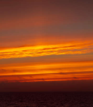 Red and orange cloudscape  of the ocean during sunrise