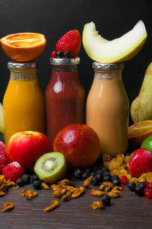 Freshly blended fruit smoothies of various colors with coconut milk and tastes in glass in wooden tray. Orange, red, green, yellow.