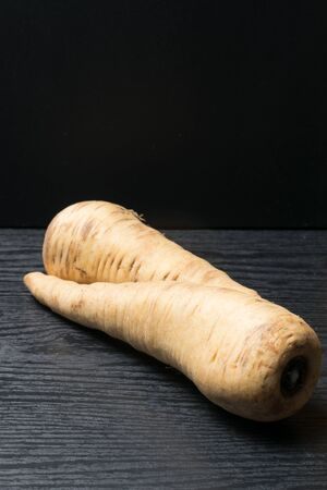 two pcs. raw organic parsley root on the black background Reklamní fotografie