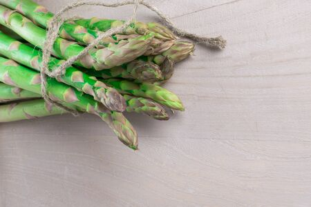 raw fresh organic green asparagus bunch on grey wooden background with whip, top view