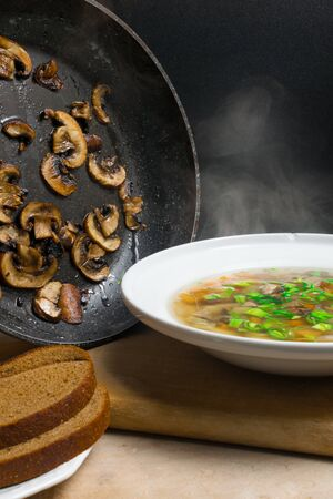 delicious hot soup with steam in bowl with mushroom and greens, and frying pan with mushroom in background Фото со стока