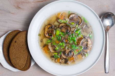 delicious mushroom soup with vegetables in white bowl on the wooden table. Vegan soup