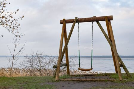 old wooden swing on the grass with view of the water and sky. Off into the wild blue yonder. Alone. Childhood