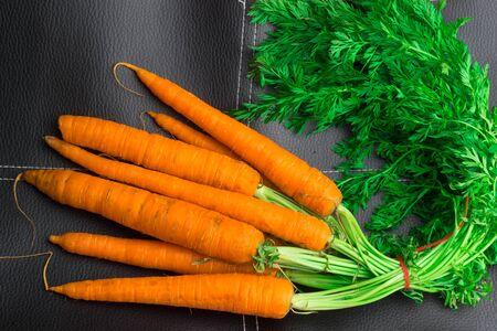 raw fresh organic carrot bunch on black table Stock Photo