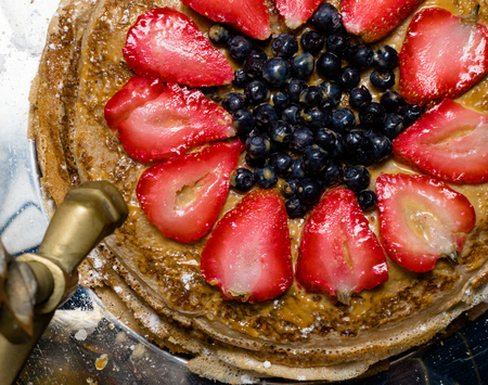 stack of freshly prepared traditional delicious pancakes cake with strawberries, blueberrys and condenset milk with honey, decorated with berry and sugar powder. Samovar Stock Photo