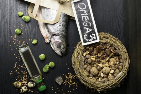 Salmón o trucha grasa saludable, aceite, nueces. Fuente de Omega 3, semillas, chía, lentejas, coles de Bruselas, huevos sobre fondo de madera oscura.