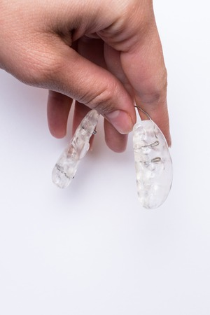 Inivisalign braces or aligner in hand. A way to have a beautiful smile and white teeth.