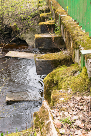 old stone bridge with green moss. River and bridge