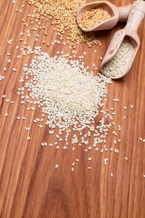 sesame seeds on the wooden background. Two type of sesame seeds in wooden spoon. Healty condiment