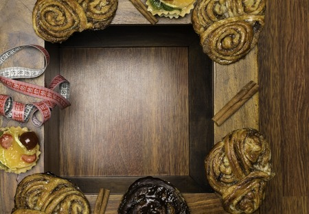 sweet cinamon and chocolate buns with tape measure, unhealthy food and diet time concept. Wooden background 版權商用圖片