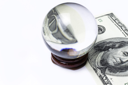 Hundred dollar bill under a magnifying glass ball is being inspected Conceptual photo isolated on white background. Selective focus 写真素材