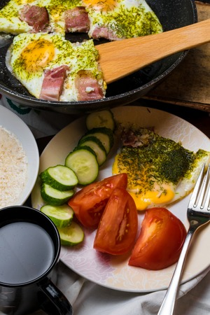 Traditional breakfast with bacon, fried eggs, tomatoes, cucumber, dill and dairy porridge in bowl. Health morning food