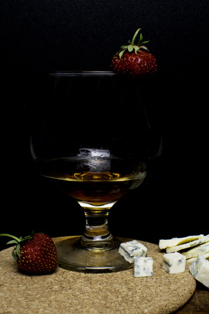 Still life with Cognac and french blue cheese on a wooden board. Glass with cognac, cheese, strawberry on a wooden background Фото со стока