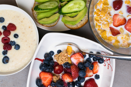 vegetarian breakfast. bowl of oat granola with milk, raw raspberries, blueberries, strawberries, and nuts with spoon for healthy breakfast and avokado and cucumber sandwich top view Stockfoto