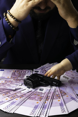 Cash Income. Businesman sitting down with his earn euro cash after a hard day, his head lowered. Man in Mens Suits. A lot of euro money. Bribe and corruption with euro banknotes. Child hand pull on gun.