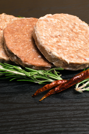 Raw Minced burger Meat with Herb and Spice Prepared for Grilling with rosemary, hot red chili, black pepper on black wooden table
