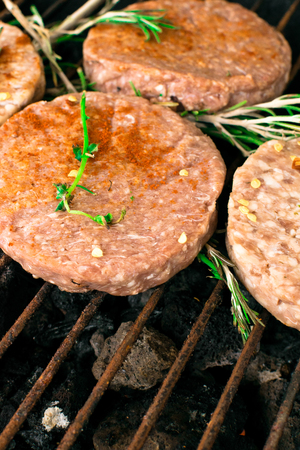 bbq burgers, with rosemary herbs, smoke and fire, copy space