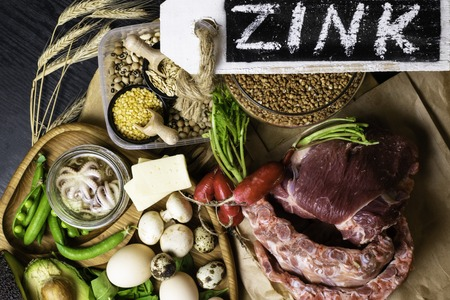 Foods Highest in Zinc as octopus, beef, buckwheat, yellow cheese, spinach, avokado,pea, mushrooms, bean, radishes eggs with inscription Healthy diet food Top view Banco de Imagens