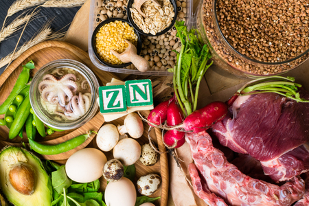 Foods Highest in Zinc as octopus, beef, buckwheat, yellow cheese, spinach, avokado,pea, mushrooms, bean, radishes eggs with inscription Healthy diet food Top view 免版税图像