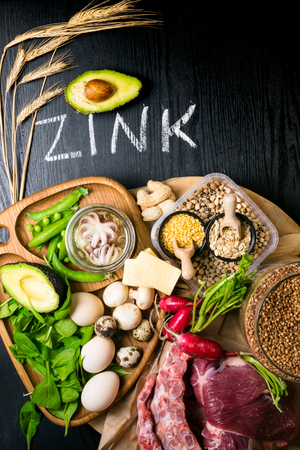 Foods Highest in Zinc as octopus in oil, beef, buckwheat, yellow cheese, spinach, avokado,pea, mushrooms, bean, radishes eggs with inscription Healthy diet food Top view Banco de Imagens